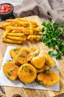 Hausgemachte gebratene hühnernuggets mit pommes frites. grauer hintergrund. draufsicht.