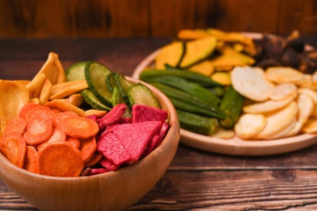 Hausgemachte gemüsechips auf holztablett. bio-diät und veganes essen.