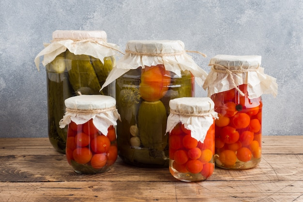Hausgemachte gemüsekonserven in dosen. eingelegte tomaten und gurken im ländlichen stil.