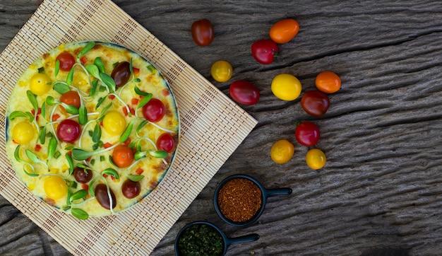 Hausgemachte gemüsepizza mit kirschtomaten und anderen bestandteilen auf einem hölzernen hintergrund