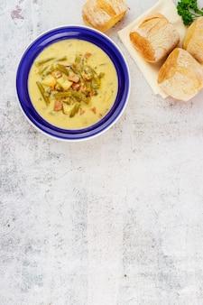 Hausgemachte gemüsesuppe mit brot in blauer platte. ansicht von oben.