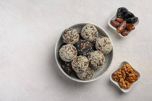 Hausgemachte gesunde energiebällchen aus früchten, nüssen, kakao, honig in einer leichten vase. neben den vasen mit datteln und walnüssen. platz kopieren. ansicht von oben