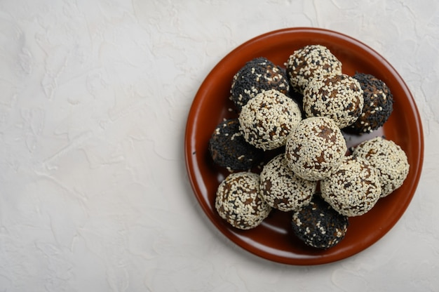 Hausgemachte gesunde energiebälle aus früchten, nüssen, kakao, honig auf einer braunen keramikplatte. ansicht von oben. platz kopieren