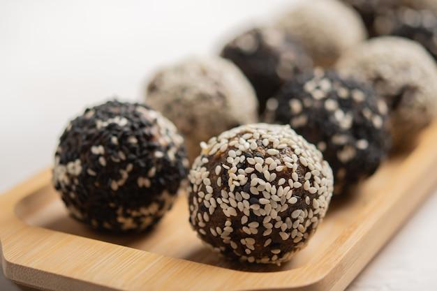 Hausgemachte gesunde energiebälle aus früchten, nüssen, kakao, honig hautnah auf holztablett... textfreiraum.