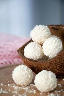 Hausgemachte gesunde süßigkeiten kokosnusskugeln in nussschale auf holzbrett.
