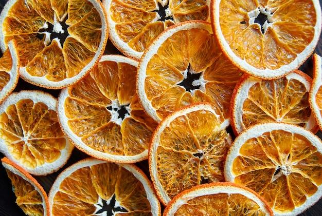 Hausgemachte getrocknete fruchtscheiben des orange grapefruits-nahrungsmittelmusters auf dunkelheit