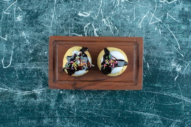 Hausgemachte glasierte kekse auf einer holzplatte, auf blauem hintergrund. foto in hoher qualität