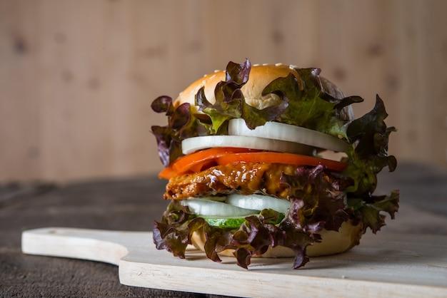 Hausgemachte hähnchenburger mit salat, tomaten und zwiebeln auf holzbrett.
