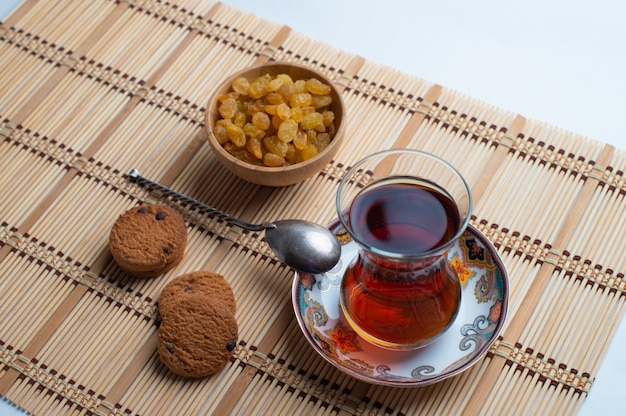 Hausgemachte haferkekse mit einer tasse tee und einer schüssel rosine