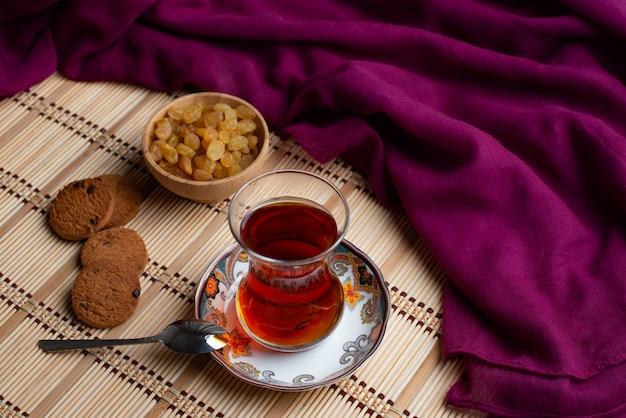 Hausgemachte haferkekse mit einer tasse tee und rosinen