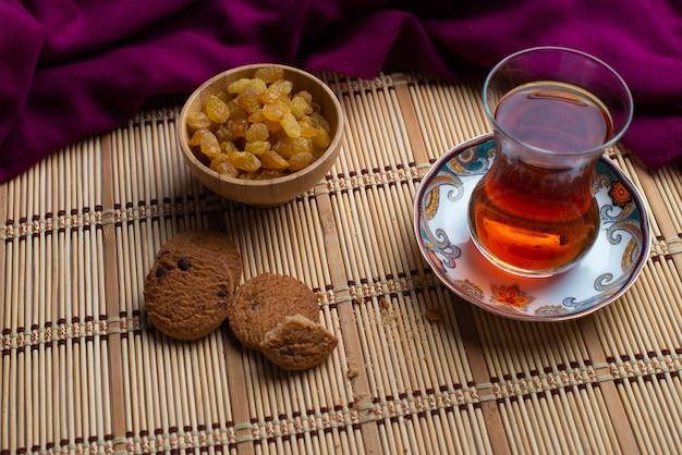 Hausgemachte haferkekse mit einer tasse türkischem tee und rosinen