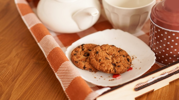 Hausgemachte haferkekse, tasse kaffee auf einem holztablett. das konzept des frühstücks im bett und ein angenehmer morgen