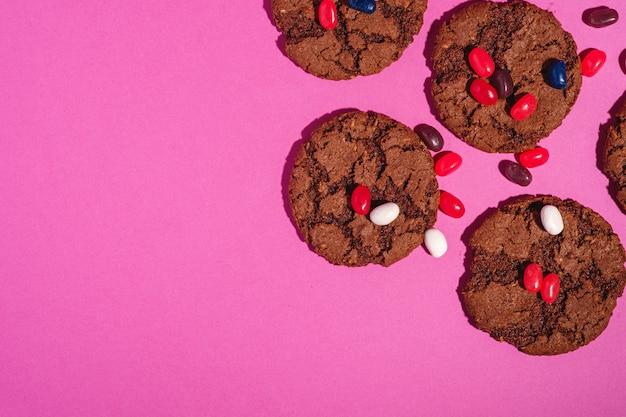 Hausgemachte haferschokoladenplätzchen mit müsli mit saftigen gummibärchen auf minimalem rosa lila hintergrund, kopierraum der draufsicht