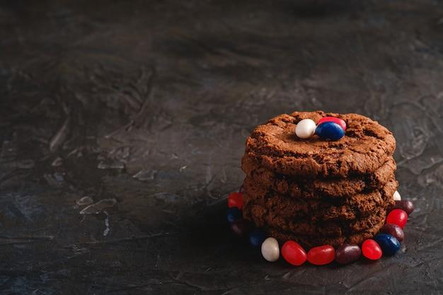 Hausgemachte haferschokoladenplätzchen stapeln mit müsli mit saftigen gummibärchen auf strukturiertem dunklem schwarz