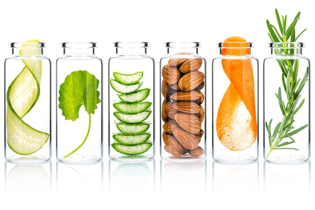 Hausgemachte hautpflege mit natürlichen inhaltsstoffen aloe vera, gurke, mandeln, centella asiatica und rosmarin in glasflaschen isolieren auf weißem hintergrund.