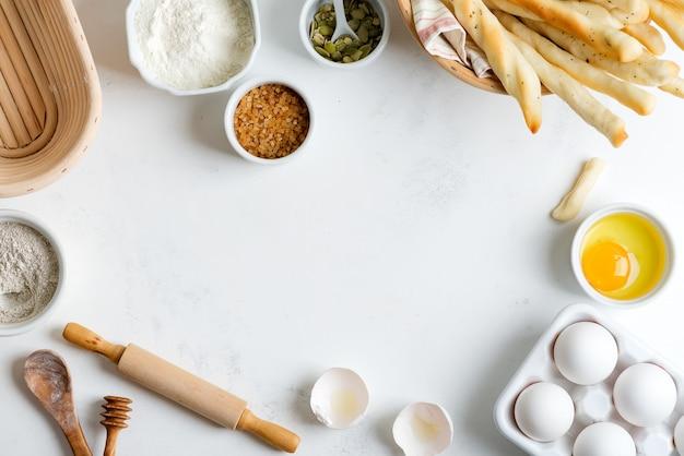 Hausgemachte herstellung von frischem, gesundem brot aus anderem gebäck aus natürlichen zutaten auf einem hellgrauen tisch.