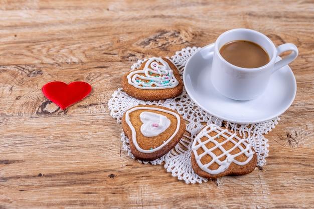 Hausgemachte herzförmige kekse mit weißem zuckerguss und streuseln mit kaffee