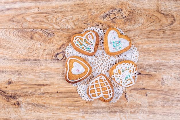 Hausgemachte herzförmige kekse verziert mit weißem zuckerguss mit streuseln