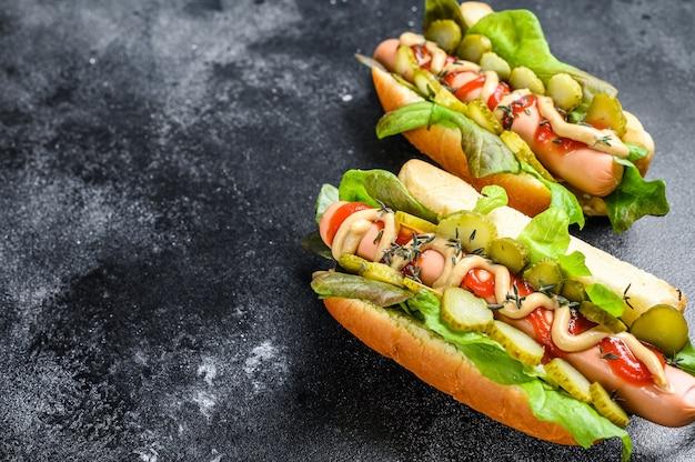 Hausgemachte hot dogs mit gemüse, salat und gewürzen. schwarzer hintergrund. draufsicht. speicherplatz kopieren.