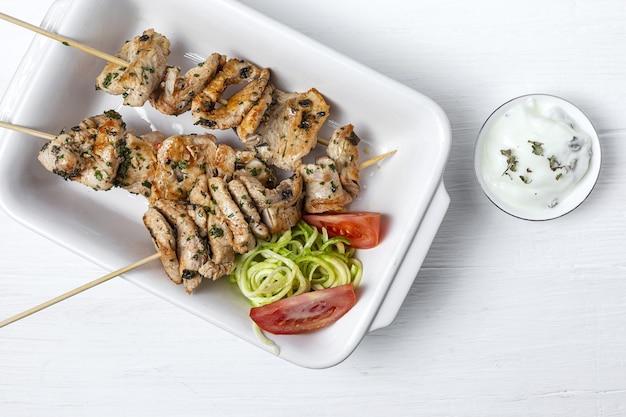 Hausgemachte hühnchen-spieße mit aromatischen kräutern und gewürzen mit joghurtsauce. arabisches essen