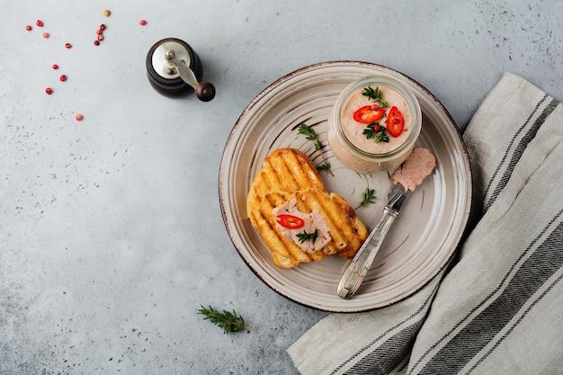 Hausgemachte hühnchenpastete aus leber mit rotem pfeffer, thymianzweigen und gerösteten brotscheiben auf altem holzbrett auf grauem beton oder stein.