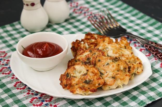 Hausgemachte hühnerpastetchen, hühnerfilet wird gebraten und mit tomatensauce auf einem teller auf dunklem hintergrund serviert