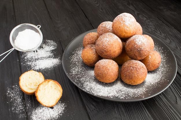 Hausgemachte hüttenkäse donuts auf dem schwarzen teller