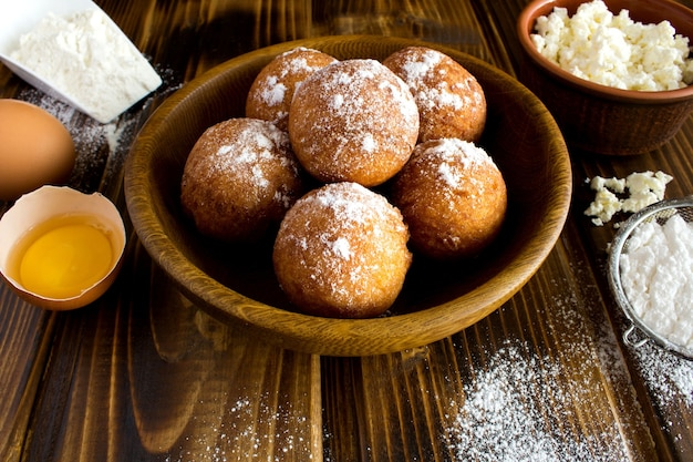 Hausgemachte hüttenkäse donuts und zutaten auf dem braunen holz