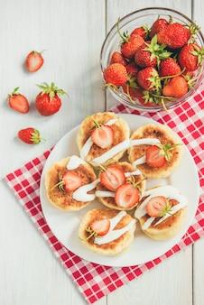 Hausgemachte hüttenkäsepfannkuchen mit saurer sahne und frischer erdbeere auf weißem hölzernem hintergrund.