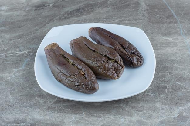 Hausgemachte in essig eingelegte aubergine gefüllte aubergine auf weißem teller.