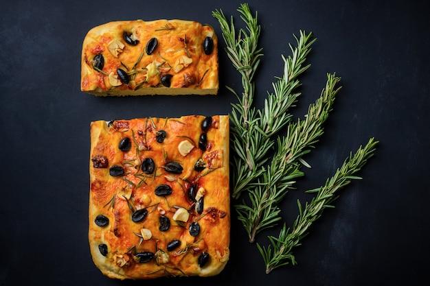 Hausgemachte italienische focaccia mit oliven und rosmarin und frisch rosmarinzweigen