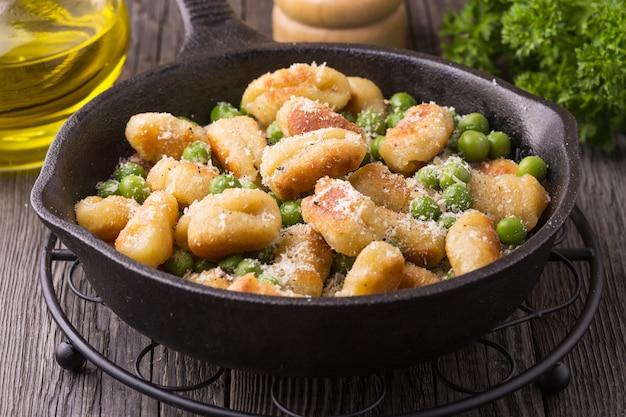 Hausgemachte italienische gnocchi mit erbsen und käse