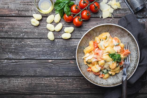 Hausgemachte italienische gnocchi mit tomaten, knoblauch, basilikum und mozzarella-käse auf holztisch