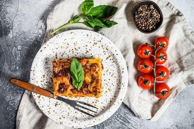Hausgemachte italienische lasagne mit tomatensauce und rindfleisch. grauer hintergrund. draufsicht