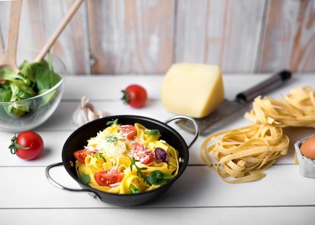 Hausgemachte italienische spaghetti-nudeln mit käse garnieren; basilikumblätter und tomatenscheibe