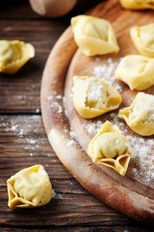 Hausgemachte italienische traditionelle tortellini auf dem holztisch