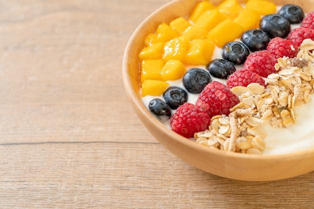 Hausgemachte joghurt-bowl mit himbeere, heidelbeere, mango und müsli - gesunder food-style