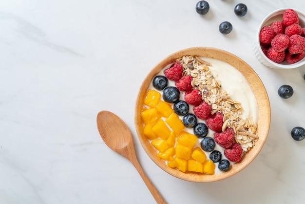 Hausgemachte joghurtschale mit himbeere, blaubeere, mango und müsli - gesunde ernährung