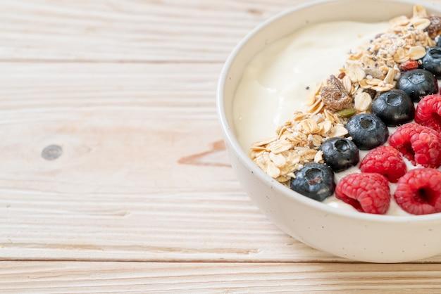 Hausgemachte joghurtschale mit himbeere, blaubeere und müsli - gesunde ernährung