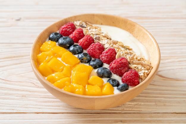 Hausgemachte joghurtschale mit himbeere, heidelbeere, mango und müsli. gesunde ernährung