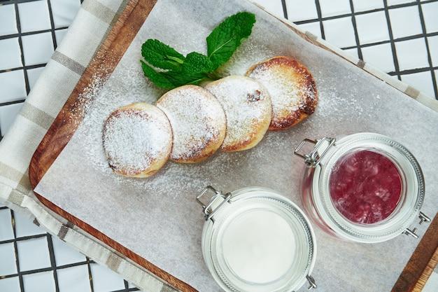 Hausgemachte käsekuchen oder syrniki mit marmelade, frischem obst und saurer sahne auf einem bastelpapier auf weißer oberfläche. ukrainische küche. frühstück