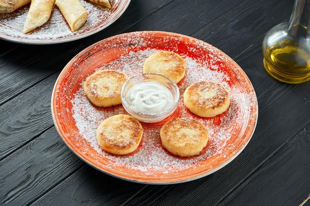 Hausgemachte käsekuchen oder syrniki mit marmelade, frischem obst und saurer sahne auf einem rosa teller