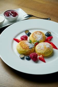 Hausgemachte käsekuchen oder syrniki mit marmelade, frischem obst und saurer sahne auf einem weißen teller. ukrainische küche. frühstück