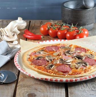 Hausgemachte käsepizza mit salami und champignons
