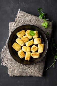 Hausgemachte kartoffel-gnocchi. flach liegen. schwarzer hintergrund.