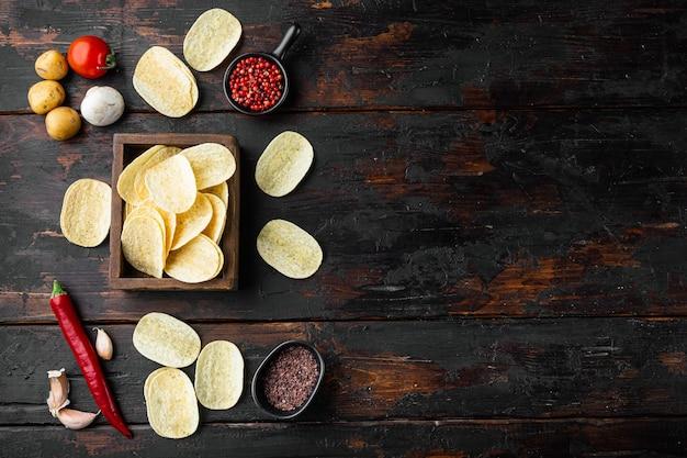 Hausgemachte kartoffelchips gesetzt, auf alten dunklen holztisch, draufsicht flach liegen