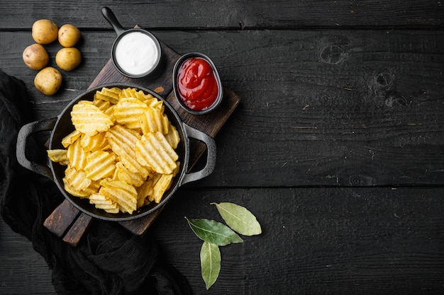 Hausgemachte kartoffelchips gesetzt, auf schwarzem holztisch, draufsicht flach liegen