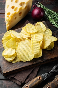Hausgemachte kartoffelchips mit käse und zwiebeln auf einem alten dunklen holztisch