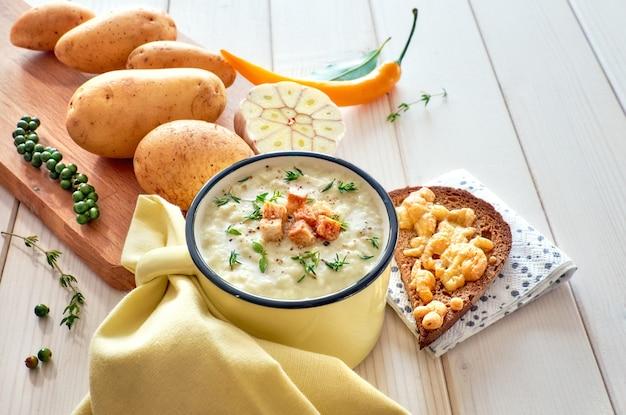 Hausgemachte kartoffelcremesuppe mit croutons, dazu geröstetes brot mit käse