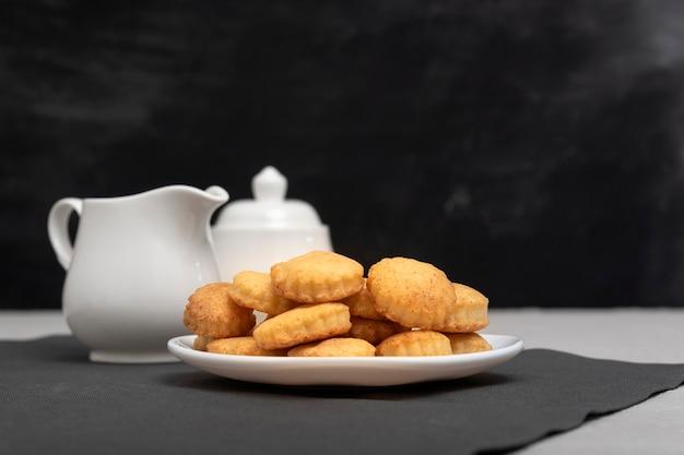 Hausgemachte kekse auf dem teller. milchkännchen und zuckerdose im hintergrund. backen für tee. leckeres frühstück.